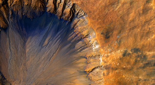 This impact crater, as seen by NASA's Mars Reconnaissance Orbiter, appears relatively recent as it has a sharp rim and well-preserved ejecta.