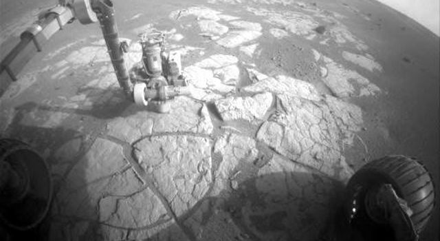 This image taken on March 13, 2009 by the front hazard-avoidance camera on NASA's Mars Exploration Rover Opportunity shows the rover's arm extended to examine the composition of a rock using the alpha particle X-ray spectrometer.