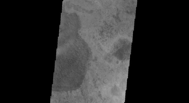 This image from NASA's Mars Odyssey shows part of Rabe Crater, featuring a portion of the dune field found on the floor of the crater on Mars. This image appears hazy due to the large amount of dust in the atmosphere from extensive dust storm activity.
