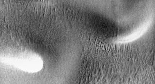 A large sand sheet with surface dune forms is located on the floor of this crater near Mars' south pole. The polar cap rests against the southern part of the sand sheet. The dune appears bright in this daytime image from 2001 Mars Odyssey spacecraft.