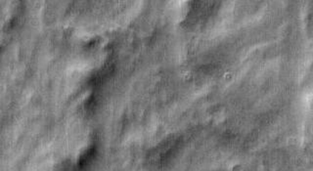 This daytime 2001 Mars Odyssey image of Terra Cimmeria shows dunes occurring both on crater floors and on the plains between the craters on Mars.
