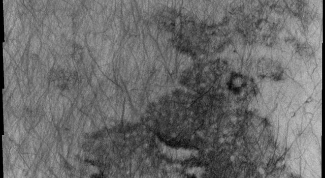 This 2001 Mars Odyssey image shows a region of Aonia Terra criss-crossed with a multitude of dust devil tracks on Mars. The tracks show up well on the dusty plains.