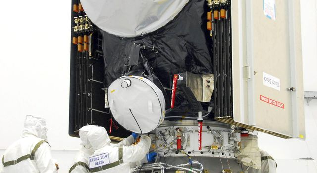 Workers secure the attachments of NASA's Dawn spacecraft onto the upper stage booster.