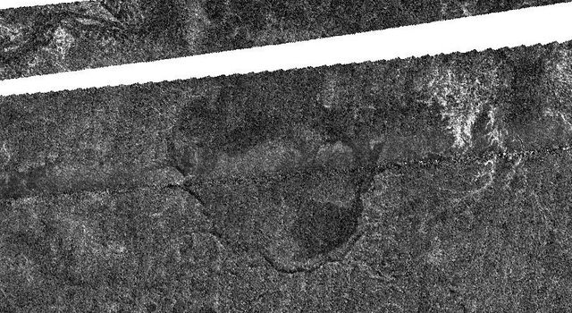An enigmatic large basin appears in the south polar region of Saturn's moon Titan at the center of this Titan Radar Mapper image from NASA's Cassini spacecraft acquired on June 22, 2009.