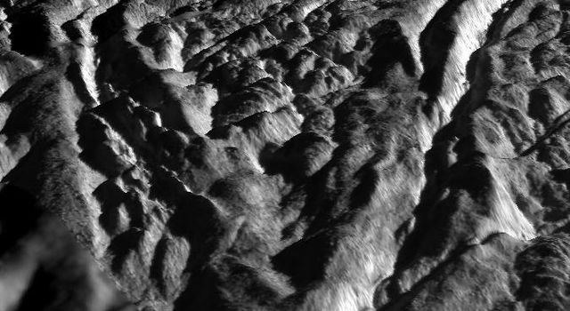 This perspective view, generated from high resolution images acquired by NASA's Cassini orbiter, highlights one of the wall scarps of the medial trough of Baghdad Sulcus on Enceladus.