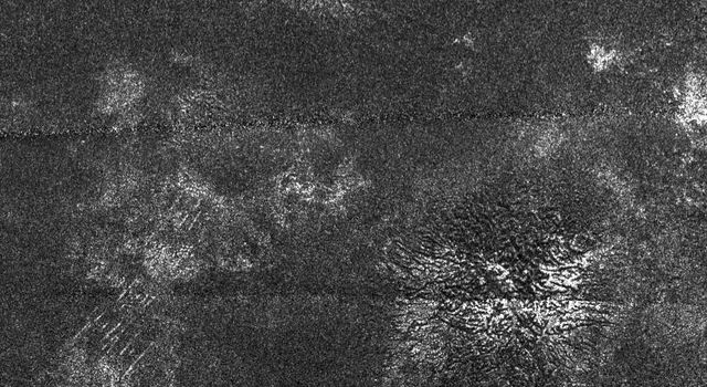 In this synthetic aperture radar image obtained by NASA's Cassini spacecraft, two generally similar features, upper center and lower right, appear to be low mountains with grooves running roughly in the up-down direction.