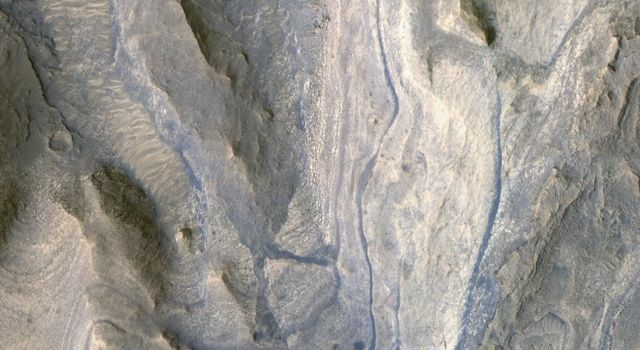 Layers of rock exposed in the lower portion of a tall mound near the center of Gale Crater on Mars exhibit variations in layer thickness and range between dark and light tones in this image taken by NASA's Mars Reconnaissance Orbiter.