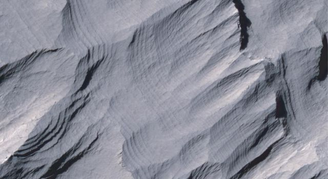 Layers of rock in the upper portion of a tall mound near the center of Gale Crater on Mars exhibit a regular thickness of several meters in this image taken by NASA's Mars Reconnaissance Orbiter.