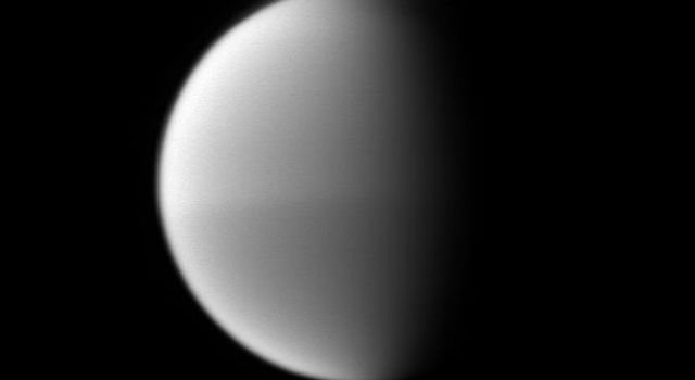 Titan's seasonal hemispheric dichotomy is chronicled in black and white, with the moon's northern half appearing slightly lighter than the dark southern half in this image taken by NASA's Cassini spacecraft.
