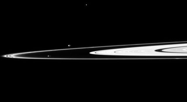 Pandora and Prometheus, the shepherding moons of the F ring, orbit inside and outside the thin ring. The elongated, potato-like shapes of the two moons are both visible in this image taken by NASA's Cassini spacecraft.