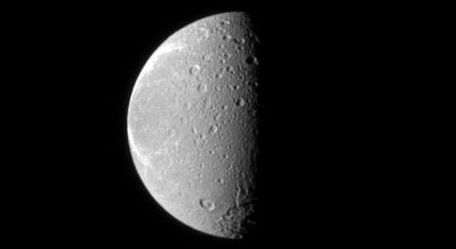 The tortured terrain of Saturn's moon Dione is documented in this NASA Cassini spacecraft image. The wispy fractures on the moon's trailing hemisphere can be seen on the left, and cratered terrain on the moon's anti-Saturn side dominates the center.