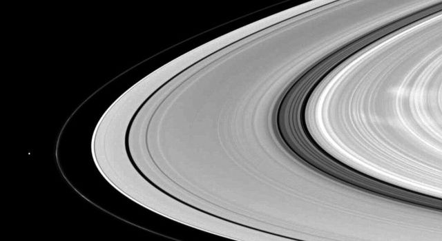 Saturn's moon Pandora shares the stage with ghostly B ring spokes in this NASA Cassini spacecraft scene. Pandora is on the left. The spokes are the radial markings visible on the right of the image.