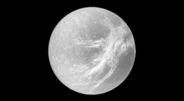 Appearing like the swirls of marble, the wispy terrain of Saturn's moon Dione is captured by NASA's Cassini spacecraft in a dramatic display of light and dark. These wispy features are a system of braided canyons with bright walls.