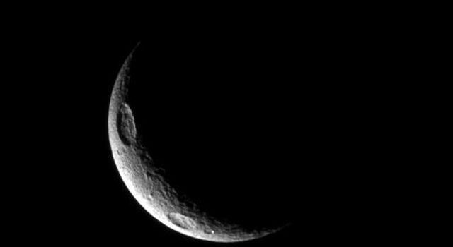 A crescent of Tethys displays two of the moon's large craters in this image taken by NASA's Cassini spacecraft. Penelope Crater can be seen at the top left. Antinous Crater is in the bottom left.