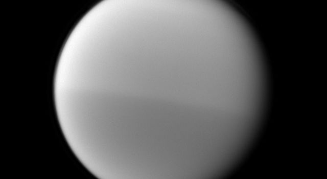 NASA's Cassini spacecraft records Titan's seasonal hemispheric dichotomy, with the moon's northern half appearing slightly lighter than the southern half in this image.