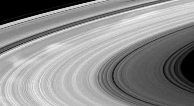 Bright spokes and the shadow of a moon grace Saturn's B ring in this NASA Cassini spacecraft image. Spokes are radial markings scientists continue to study, and they can be seen here stretching from the far left to upper right of the image.