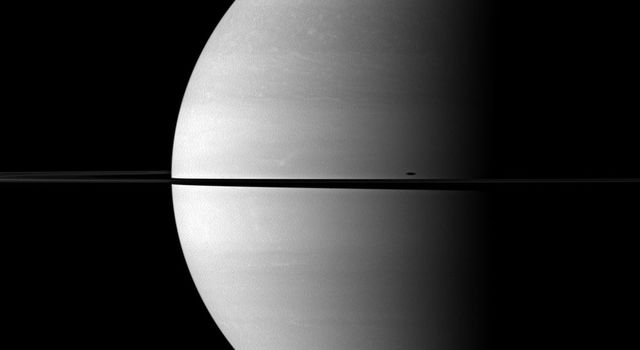 The shadow of Saturn's moon Mimas is elongated across the planet in this image from NASA's Cassini spacecraft. The moon itself is not shown, but the shadow appears just above the ringplane on the right of the image.