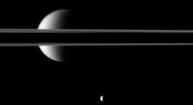 Saturn's rings, partially darkened by the planet's shadow, cut a striking figure before Saturn's largest moon, Titan. The moon Mimas is near the bottom of this image taken by NASA's Cassini spacecraft..