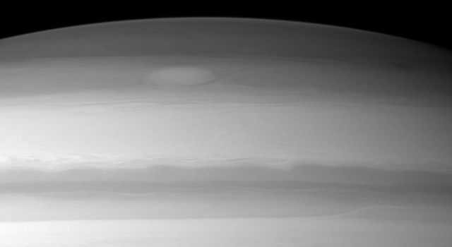A large cloud formation swirls through the high northern latitudes of Saturn near the top of this image taken by NASA's Cassini spacecraft.