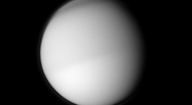 Two different seasons on Titan in different hemispheres can be seen in this image. The moon's northern half appears slightly darker than the southern half in this view taken in visible blue light by the Cassini spacecraft.