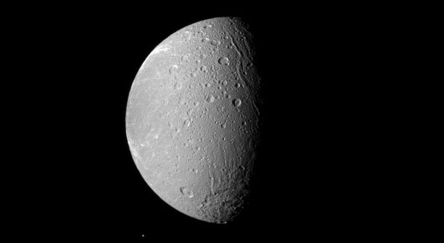 Saturn's moon Dione dwarfs the moon Telesto in this image captured by NASA's Cassini spacecraft image. Dione is the fourth largest of Saturn's moons, and it dominates this view. Tiny Telesto can be seen below and to the left of Dione.