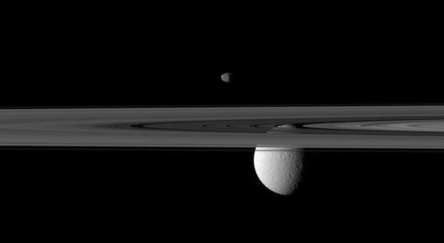 Saturn's rings occupy the foreground of this image captured by NASA's Cassini spacecraft. The small moon Janus appears to hover above, while the far larger moon Rhea is partially obscured by the rings.