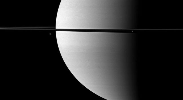 Resembling ornaments hanging from Saturn's rings, two moons accent this portrait of the planet captured by NASA's Cassini spacecraft. The moon Enceladus is on the right. Dione is on the left.
