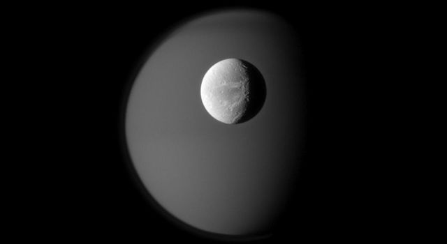 "The surface of Saturn's moon Dione is rendered in crisp detail against a hazy, ghostly Titan. A portion of the ""wispy"" terrain of Dione's trailing hemisphere can be seen on the right in this captured by NASA's Cassini spacecraft."