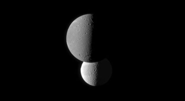 Saturn's moon Dione, in the foreground of this image from NASA's Cassini spacecraft, appears darker than the moon Tethys. Tethys appears brighter because it has a higher albedo than Dione, meaning Tethys reflects more sunlight.