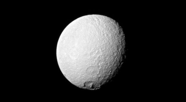 NASA's Cassini spacecraft looks toward an area between the trailing hemisphere and anti-Saturn side of Tethys and spies the large crater Melanthius near the moon's south pole.