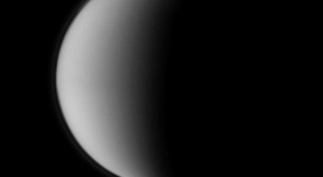 Crisp details on Dione contrast with the haziness of Titan in image from NASA's Cassini spacecraft of a pair of Saturn's moons. Smaller Dione is at the bottom of the image, and that moon's wispy terrain is visible.
