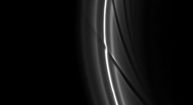 The gravity of potato-shaped Prometheus periodically creates streamer-channels in the F ring, and the moon's handiwork can be seen in the dark channels in this image from NASA's Cassini spacecraft.