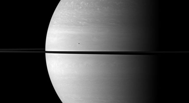The immense size of Saturn is emphasized in this portrait by NASA's Cassini spacecraft that features the moon Mimas shown in front of the planet. Mimas appears as only a small dot above the rings near the center of the image.