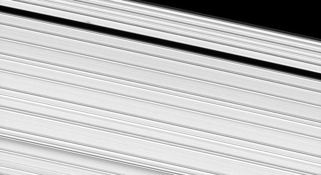 A propeller-shaped structure, created by an unseen moon, can be seen in Saturn's A ring and looks like a small, dark line interrupting the bright surrounding ring material in the upper left of this image taken by NASA's Cassini spacecraft.