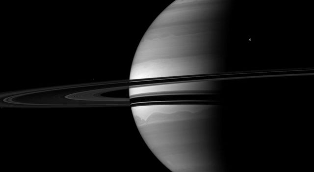 Four of Saturn's moons join the planet for a well balanced portrait. Titan, Saturn's largest moon, is in the lower left. Tethys appears in upper right. The smaller moons Pandora and Epimetheus are barely visible here.