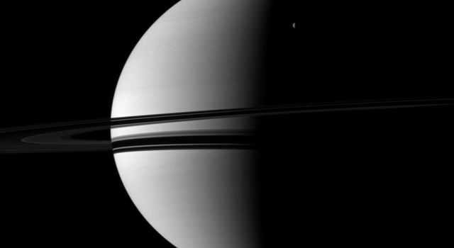 A small crescent of the moon Rhea is dwarfed by the larger crescent of Saturn in this image captured by NASA's Cassini spacecraft. Rhea can be seen in the upper right of the image.