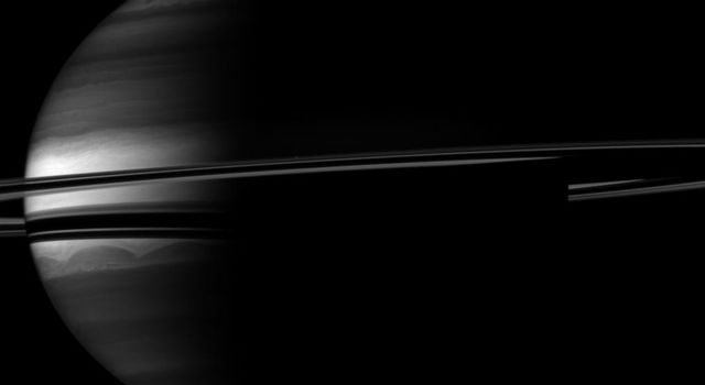 A crescent Saturn appears nestled within encircling rings in this image captured by NASA's Cassini spacecraft. Clouds swirl through the atmosphere of the planet. Prometheus appears as a speck above the rings near the middle of the image.