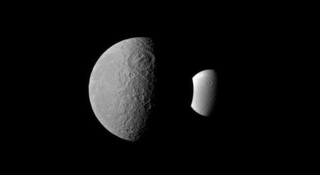 Rhea and Dione seem like dark and light fraternal twins in this image from NASA's Cassini spacecraft, with each of these two Saturnian moons displaying a large crater oriented similarly in the northern hemisphere.