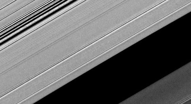 A propeller-shaped structure created by an unseen moon appears dark in this image obtained by NASA's Cassini spacecraft of the unilluminated side of Saturn's rings. The propeller is marked with a red arrow in the top left.