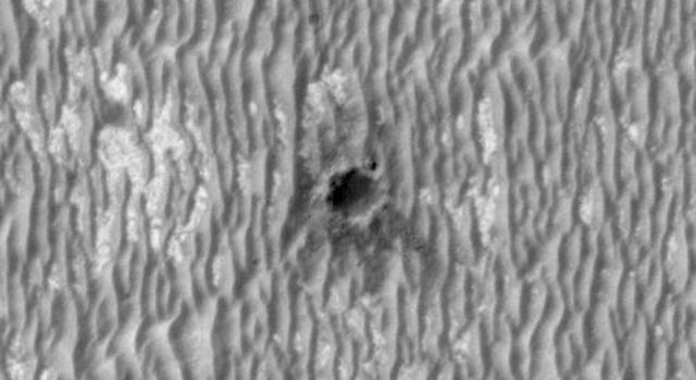 This image, acquired by NASA's Mars Reconnaissance Orbiter, shows the rover Opportunity perched on the edge of 'Concepción' crater, a fresh crater with dark rays that clearly overprint the north-trending, wind-shaped ripples, in Meridiani Planum.