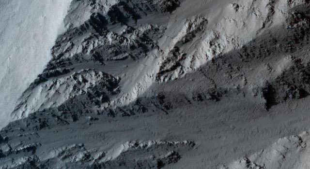 This image taken by NASA's Mars Reconnaissance Orbiter covers the northern edge of the largest volcano in the solar system, Olympus Mons on Mars; its margin is defined by a massive cliff many kilometers (several miles) tall.