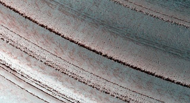 The Martian north polar layered deposits are an ice sheet much like the Greenland ice sheet on the Earth in this image from NASA's Mars Reconnaissance Orbiter. This Martian ice sheet contains many layers that record variations in the Martian climate.