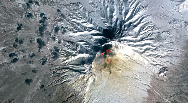 Sheveluch Volcano in Kamchatka, Siberia, is one of the frequently active volcanoes located in eastern Siberia. In this image from NASA's Terra spacecraft, brownish ash covers the southern part of the mountain, under an ash-laden vertical eruption plume.