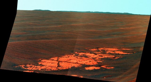 NASA's Mars Exploration Rover Opportunity used its panoramic camera (Pancam) to capture this false-color view of the rim of Endeavour crater, the rover's destination in a multi-year traverse along the sandy Martian landscape.