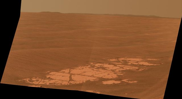 NASA's Mars Exploration Rover Opportunity used its panoramic camera (Pancam) to capture this view approximately true-color view of the rim of Endeavour crater, the rover's destination in a multi-year traverse along the sandy Martian landscape.