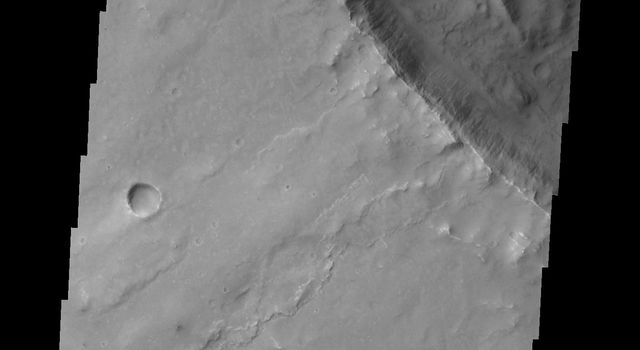 This image captured by NASA's 2001 Mars Odyssey shows a landslide deposit located in an unnamed crater in Syrtis Planum.