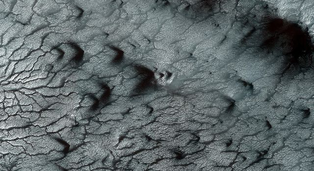 Southern spring on Mars brings sublimation of the seasonal dry ice polar cap as seen by NASA's Mars Reconnaissance Orbiter.