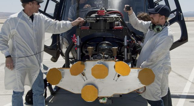 In advance of a testing flight at NASA Dryden Flight Research Center, members of the test team prepare the engineering model of the Mars Science Laboratory descent radar on the nose gimbal of a helicopter. The yellow disks are the radar's antennae.