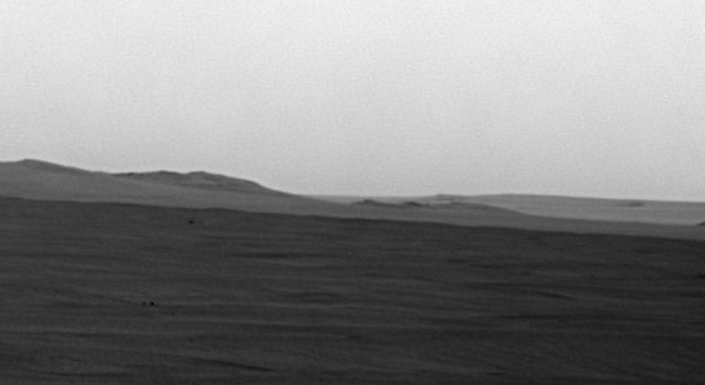 This image from NASA's rover Opportunity shows mostly a portion of Endeavour's western rim (left); a paler-looking terrain on the horizon beyond Endeavour (right) is part of a thick deposit of material ejected by the impact that excavated Iazu Crater.