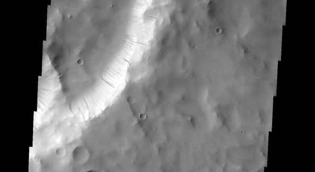 NASA's 2001 Mars Odyssey captured dark slope streaks, like the ones on the rim of a unnamed crater in Terra Sabaea, are thought to have been formed by material moving down slope due to gravity.